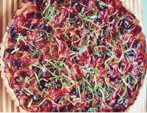 Savory Tart with Caramelized Onions, Cherry Tomatoes, Black Olives, and Basil.
