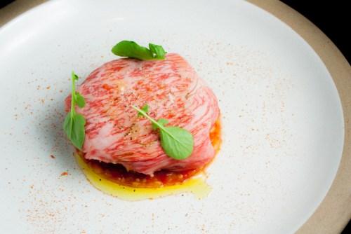 Tomato Panzanella with Miyazaki Ribeye Beef Carpaccio, Seaweed Focaccia, Padron Pepper Aioli, Avocado, and Tomato Powder.
