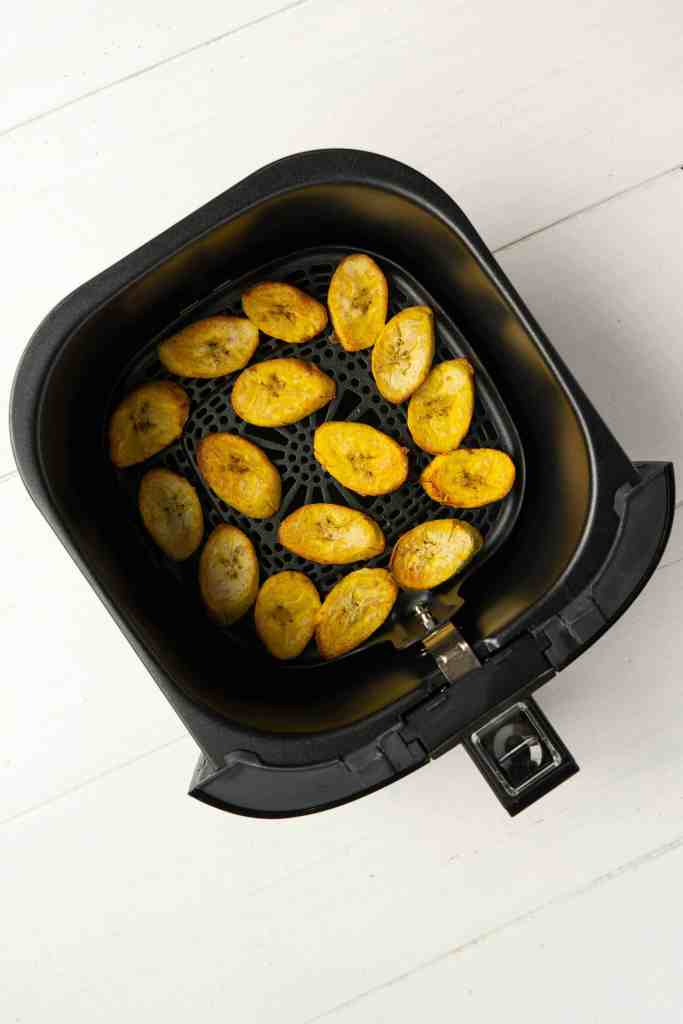 An air fryer loaded with plantain chips.
