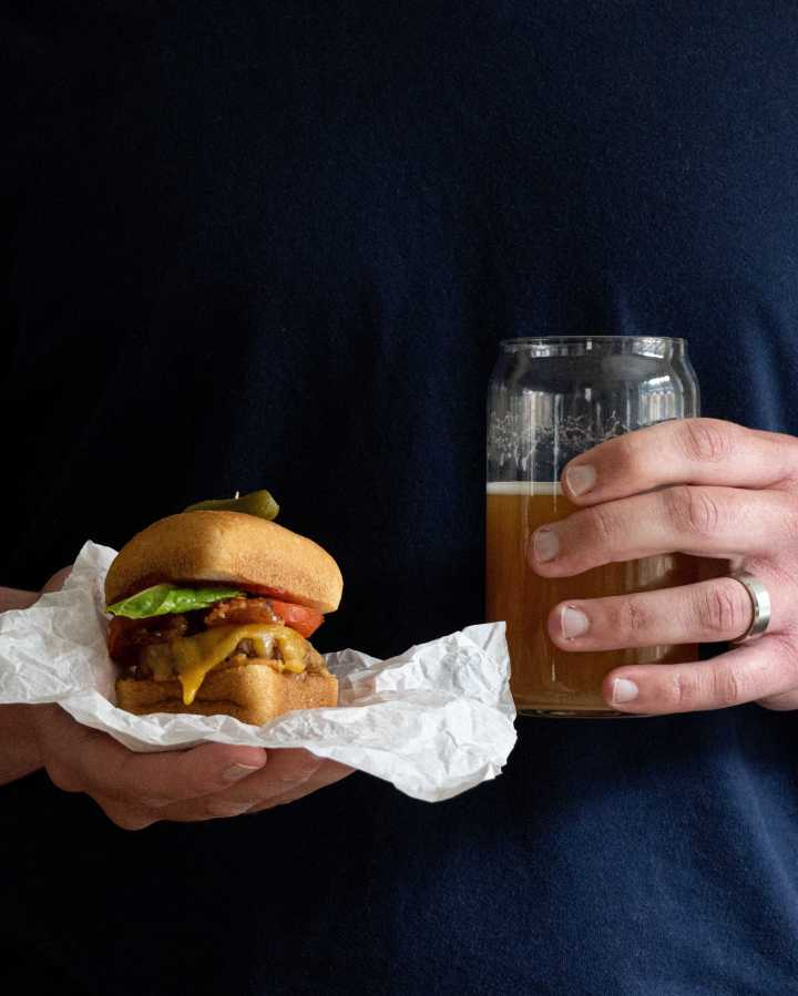 A dad holding a cheeseburger slider and a beer.