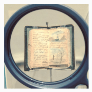 Magnifying classes to view tiny books in the Charlotte Bronte display at the Morgan Library