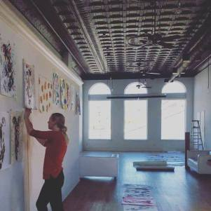 Sally hanging artwork in gallery