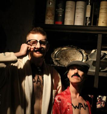two people wearing mustaches in a library