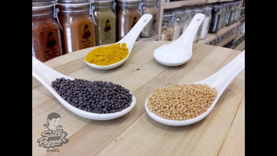 Cuatro cucharas llenas de especias para hacer salsa de mostaza y sus variantes: mostaza amarilla, mostaza negra,curcuma y sal.