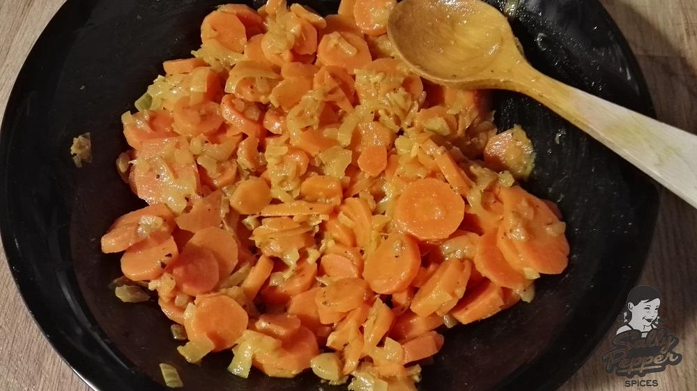 En una ensaladera, mezclar con la ayuda de una cuchara de madera, las zanahorias junto con la cebolla con ajo, el zumo de limón y un chorrito de aceite de oliva.