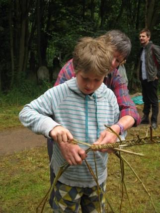 child plaiting with rush