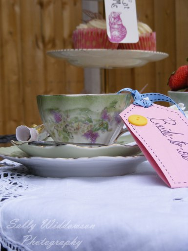 Handmade bride-to-be name tag with ribbon and button on vintage tea set place setting