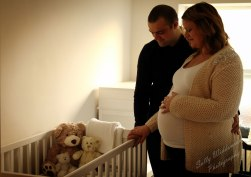Pregnant couple in nursery with cot waiting for baby for maternity photography session indoors