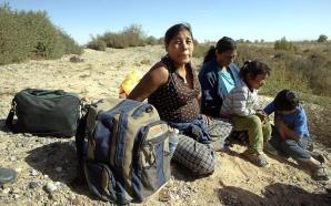 ACOMPA—A DOCUMENTO: DECIMO ANIVERSARIO TLC. Una familia de supuestos migrantes ilegales permanece sentada en las inmediaciones de la frontera de Mexico con EEUU en San Isidrio, Estado de Chihuahua, el 26 de noviembre de 2003. AFP PHOTO/Jorge UZON / AFP PHOTO / JORGE UZON