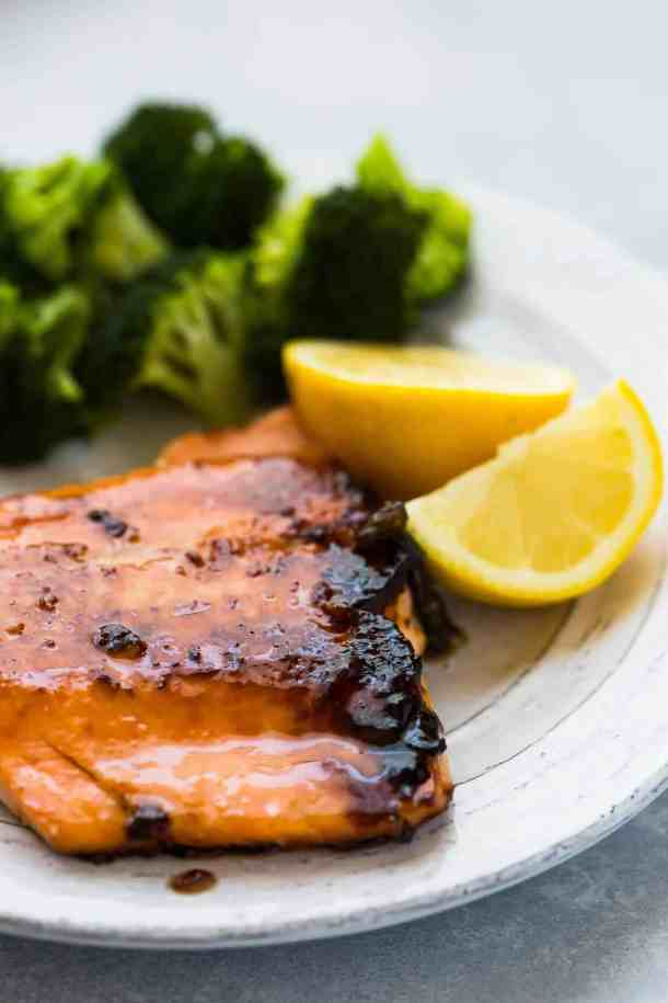 salmon fillet on a white plate, with a brown sugar crusted top. Lemons and broccoli in the background.