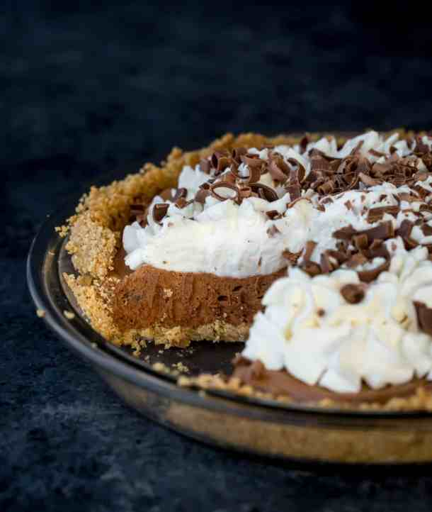 French silk pie topped with whipped cream and chocolate curls.