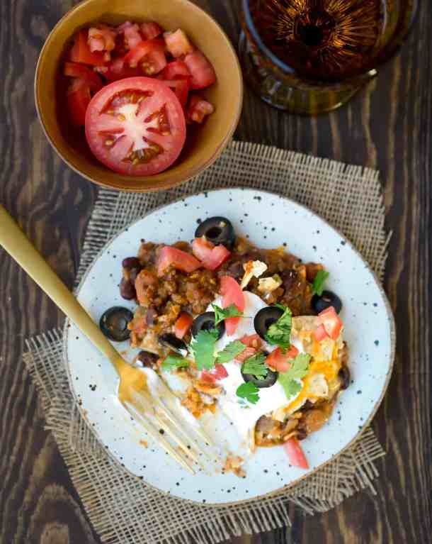 Mexican lasagna topped with tomatoes, olives, and cilantro.