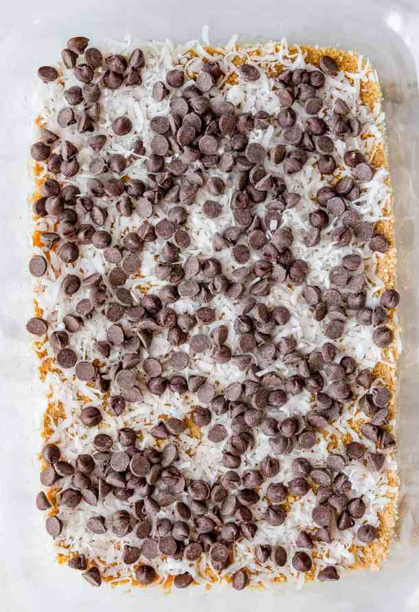 7 Layer Bars in the making, with graham cracker crust, shredded coconut, and chocolate chips layered in a 9x13 inch pan.