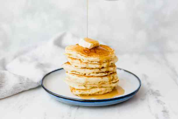 Delicious homemade buttermilk pancakes, from scratch, stacked high with maples syrup poured over top.