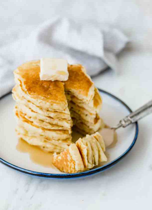 Homemade buttermilk pancakes stacked on a plate, with a square of butter on top and maple syrup down the sides.