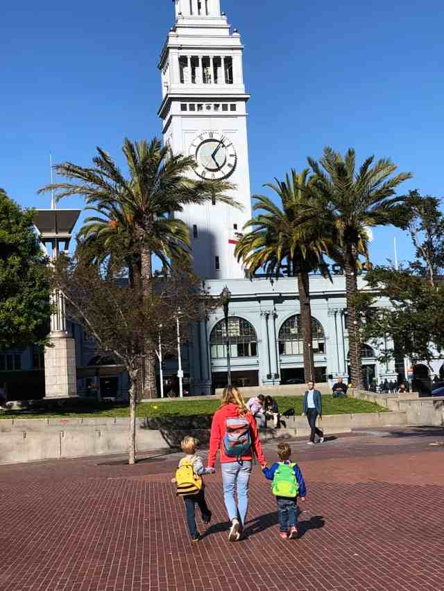 Mom with two young boys walking towards the Ferry Building in San Francisco, CA. Backpacks are a great holiday gift for travelers