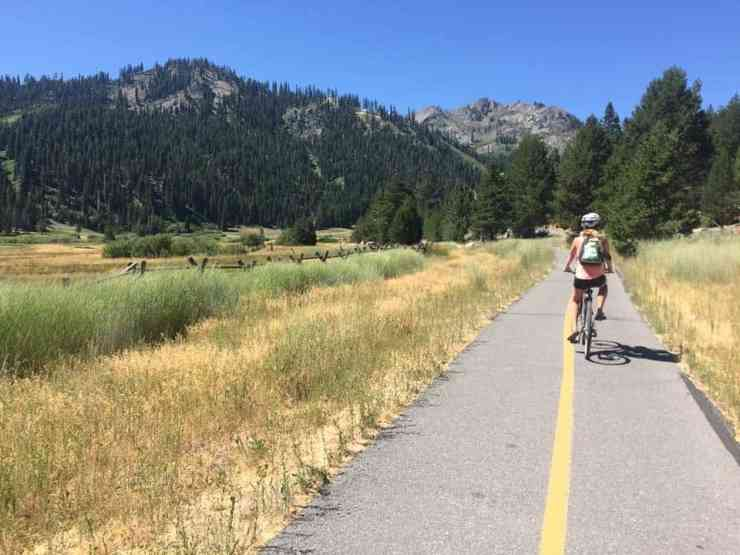 bike path leading through a meadow in the Sierra Nevadas. Woman riding her bike towards the mountains