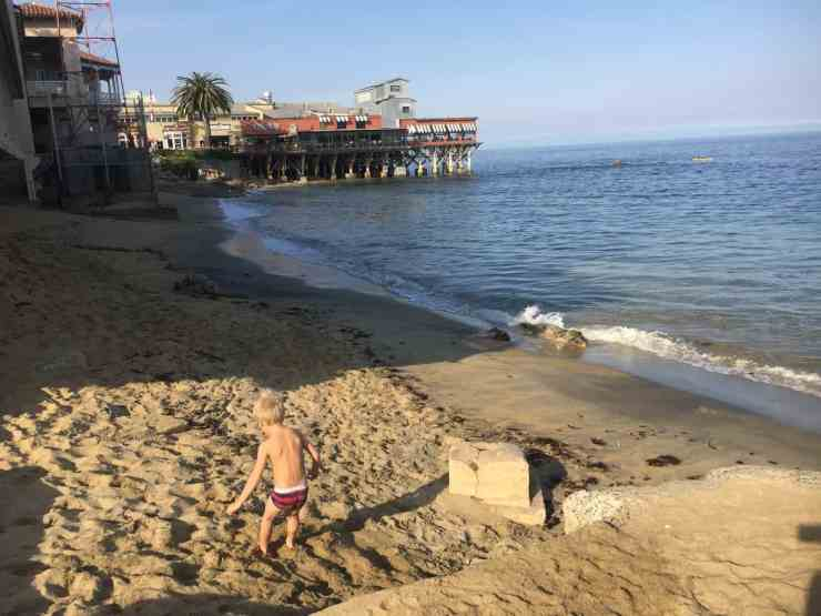 child jumping into sand at McAbee beach in Monterey, CA