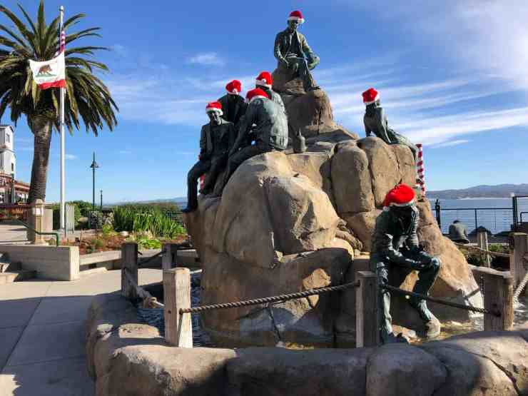 Santa hats on statues n the fountain in Steinbeck Plaza