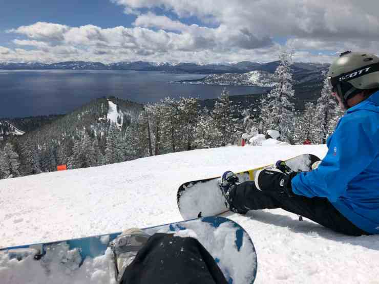 Two snowboarders sitting at the top of the mountain looking down at Lake Tahoe