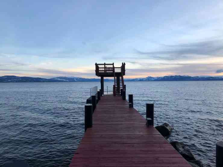 A dock jutting out into the lake at Lake Tahoe. Pink sky with wispy gray clouds.