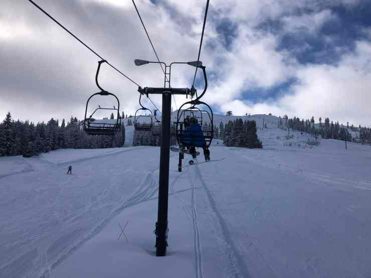 dad and young son on a chairlift with a empty ski hill below them. soda springs is one of the best places to ski in lake tahoe with kids