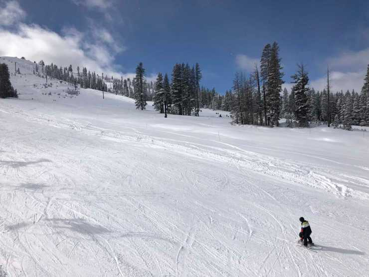 groomed ski hill with parent teaching child how to ski.