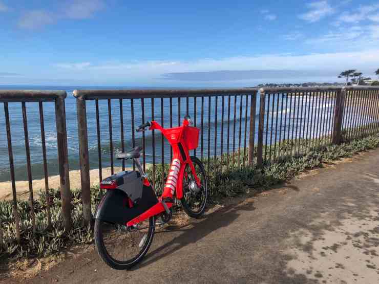 bright red jump bike leaned up against a fence on a path next to the ocean