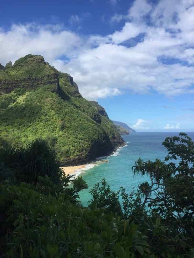 Towering green mountains that come down to aqua blue waters off the Na Pali coast in Kauai