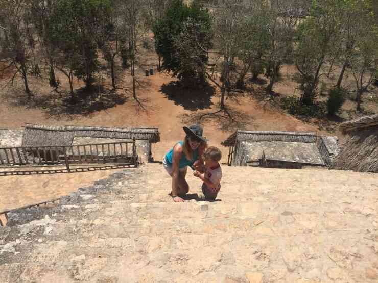 A mom in a black sun hat climbing the steps of Mayan ruins with a small toddler