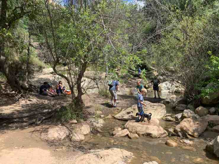 people playing in the water and picnicking at a creek. head upstream to go to take the Seven Falls trail. or go straight to inspiration point