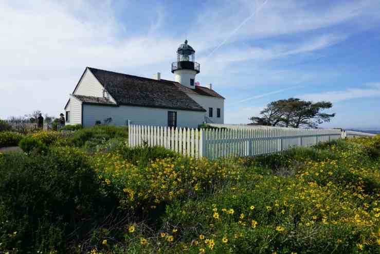 wildflowers in front of a small white lighthouse in Point Loma, CA