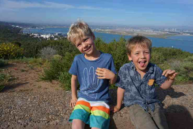 little boys sitting on a bench at Cabrillo National Monument with the San Diego skyline in the background