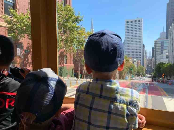 Two boys looking out the window of a cable car in San Francisco, CA.