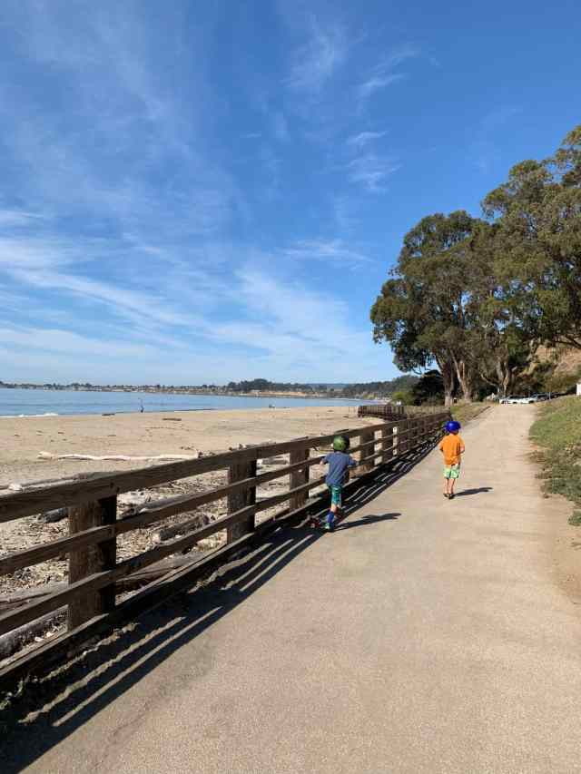 Two boys doing scooters along a paved path next to the beach at Seacliff State Beach in Santa Cruz CA. Seacliff is the perfect place to walk with toddlers in Santa Cruz.