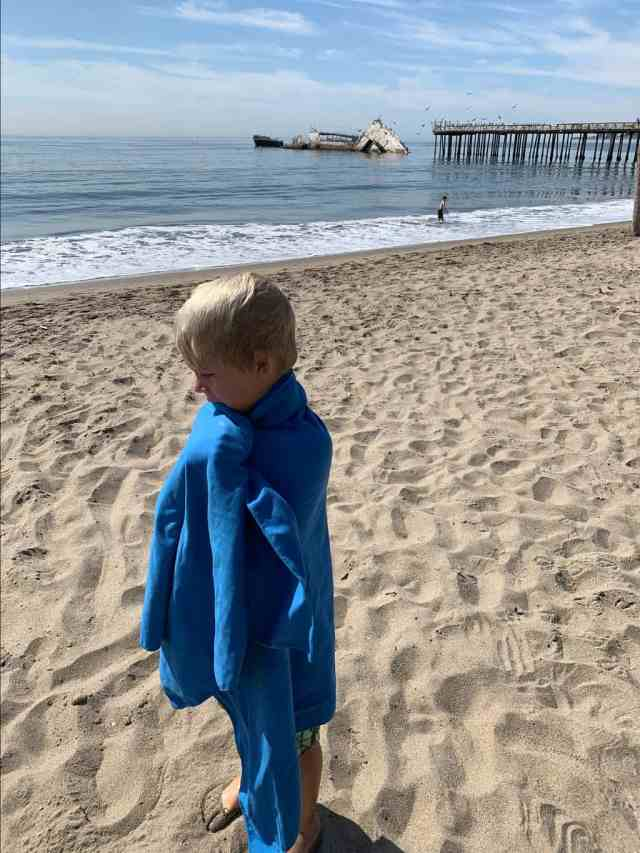 boy wrapped in a towel at the beach. a microfiber travel towel is the perfect holiday gift for a traveler.