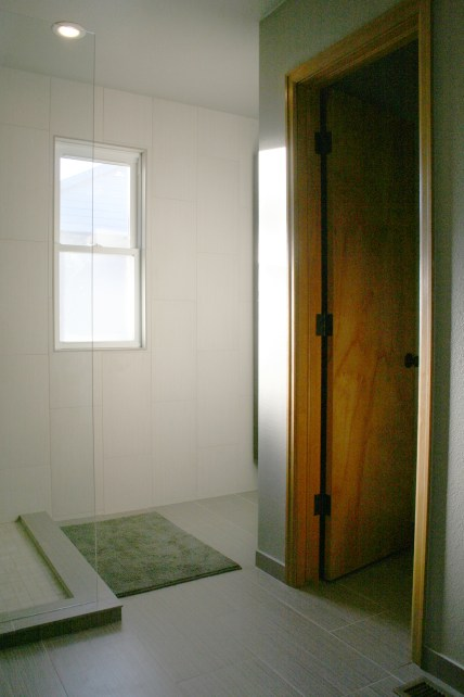 A glass panel shower wall keeps the bathroom feeling spacious and clean