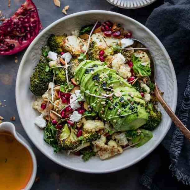 This healthy glow broccoli and lemon winter salad is the perfect mid winter nourish bowl. Roasted broccoli and cauliflower drizzled with a lemon garlic dressing and topped with all the winter essentials. Pomegranate, toasted almonds and goat's cheese.#veggie #plantbased #salad #wintersalad