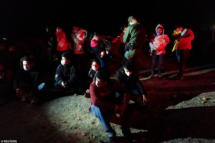 Asylum-seeking migrant families wait to be transported by Border Patrol after crossing the Rio Grande river into the U.S. Monday night