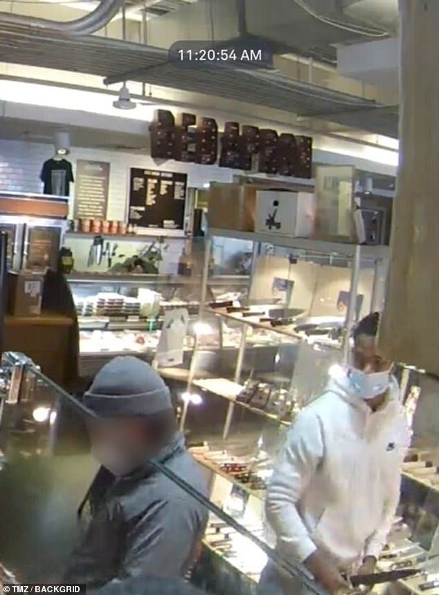 Green is seen in a white hoody and face mask, buying a $300 knife on Friday morning in DC