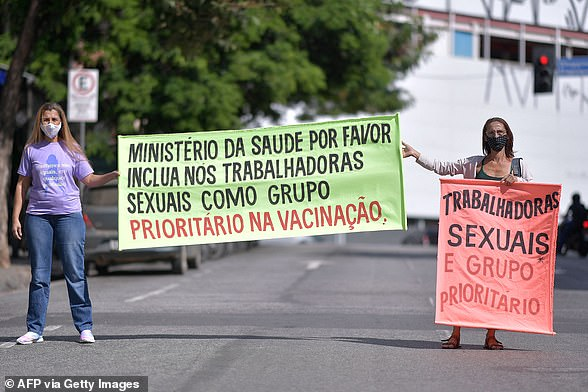 Sex workers in a Brazilian city have gone on strike for a week, demanding to be included in the group of front-line workers receiving priority coronavirus vaccine. Pictured: Women hold signs saying: 'Health ministry please include us sex workers as a priority vaccine group' and 'Sex workers are a priority group'