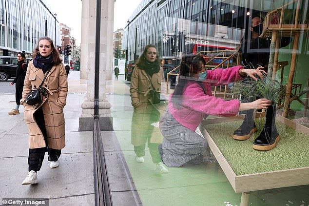 A Selfridges employee puts the final touches to the window display at the store on Oxford Steet in London today