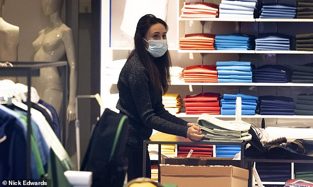 A worker at Lacoste on Regent Street unpacks clothes as she puts them on the shelves yesterday ahead of the reopening