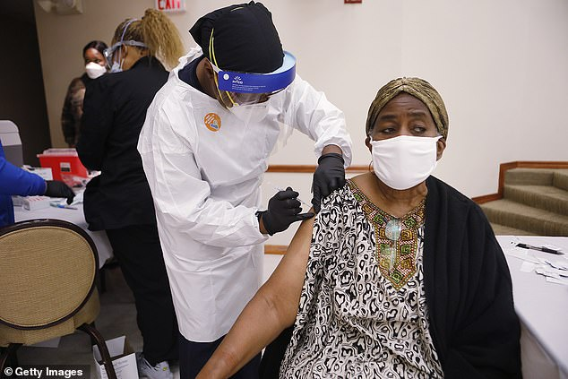 On Thursday, the CDC launched a new initiative to take steps to address the effects of racism, saying the life expectancy of 'non-Hispanic/Black Americans' is four years lower than that of their white counterparts. Pictured: A Florida woman receives the Covid-19 vaccine at the St. Johns Missionary Baptist Church in Tampa in January [File photo]