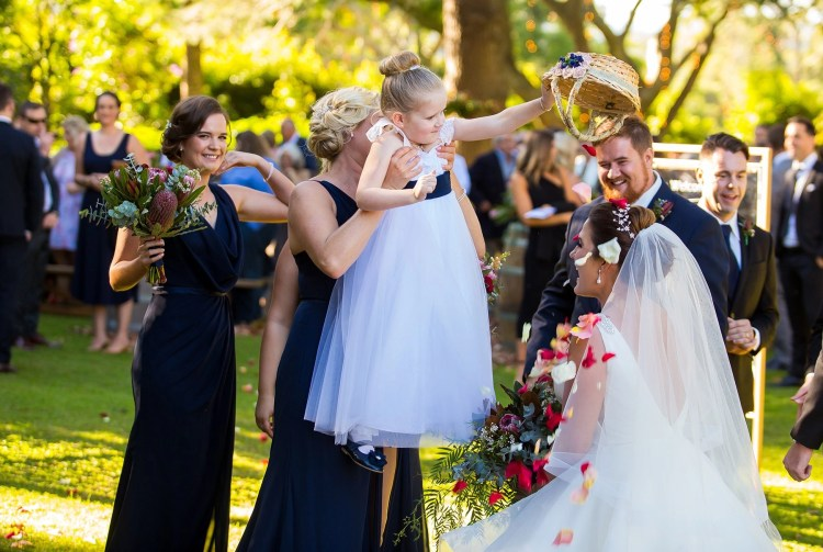flowergirl pouring petals on bride and groom