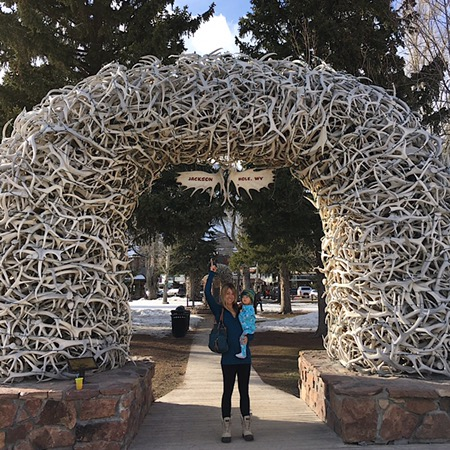 Mom and baby under antler arch Jackson, WY