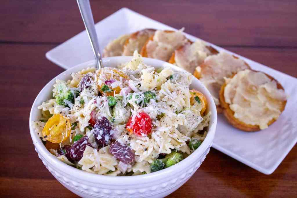 pasta salad in a white bowl with a fork and garlic toast on a white plate behind