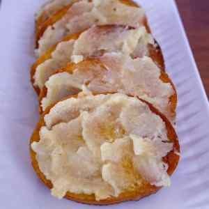 roasted garlic on bread on a white plate