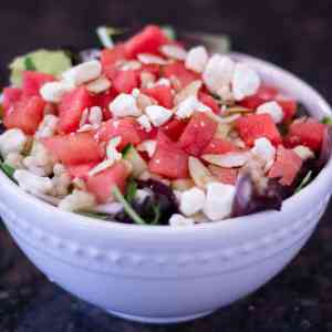 watermelon salad in a white bowl with a dark background