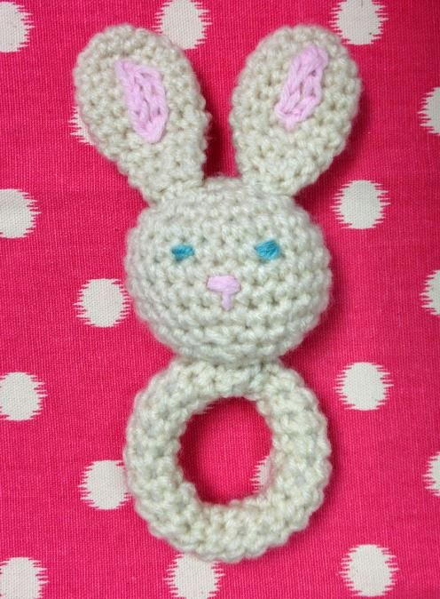 A crochet baby toy bunny on a pink background